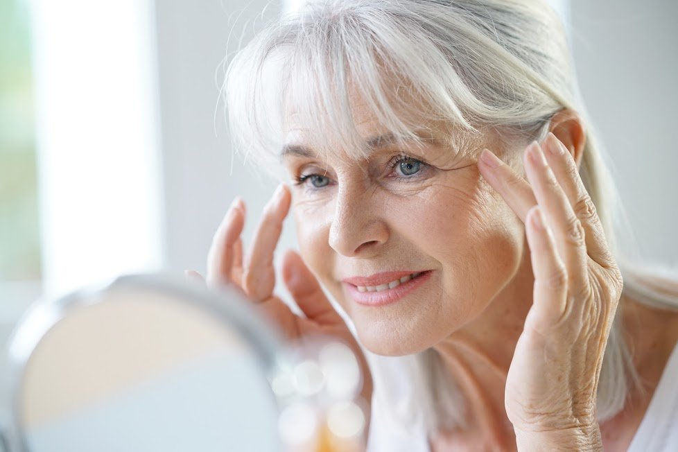 Elderly woman looking at her face in mirror